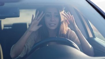 Young woman sitting scared in car